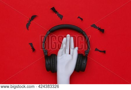 Mannequin Hand And Stereo Headphones With Bats On Red Background