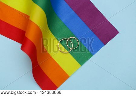 Lgbt Wedding. Lgbt Rainbow Flag And Golden Rings On Blue Background. Tolerance, Freedom