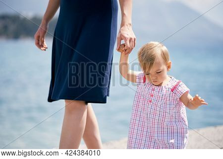 Mom Leads The Little Girl By The Hand Along The Breakwater. Close-up