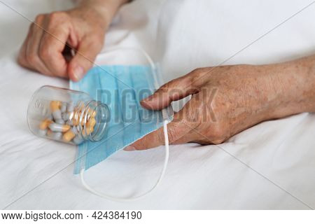 Elderly Woman With Pills In Wrinkled Hands On Medical Mask. Taking Medication In Capsules During Cor