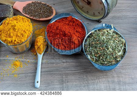 Colorful Culinary Spices And Clock On Wooden Surface