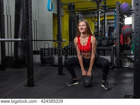 Young Attractive Woman In Sportswear Practices Exercise With Heavy Kettlebell  In Modern Gym. Free W