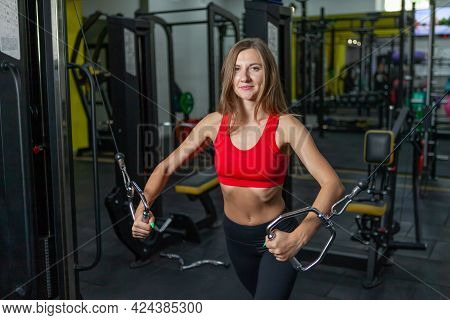 Smilling Fit Woman Flexing Muscles On Gym Machine. Girl Execute Exercise With Exercise-machine Cable