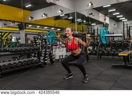 Young Slim Fit Woman Practicing Squats With A Barbell On Her Shoulders In A Modern Gym