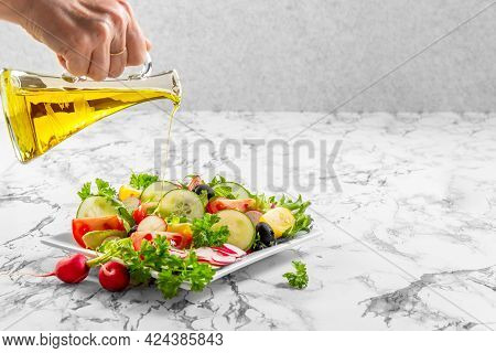 Fresh Chopped Vegetables In A Plate And Salad Bowl. Hand Pours Olive Oil From A Bottle. Healthy Eati