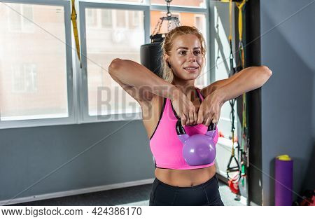Strong Blonde Woman Exercising With A Kettlebell Weight. Free Weights Training