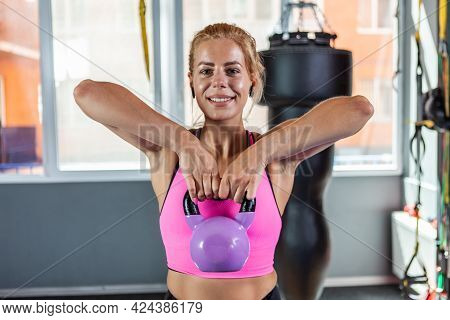 Muscular Strong Blonde Woman Exercising With A Kettlebell Weight. Free Weights Training