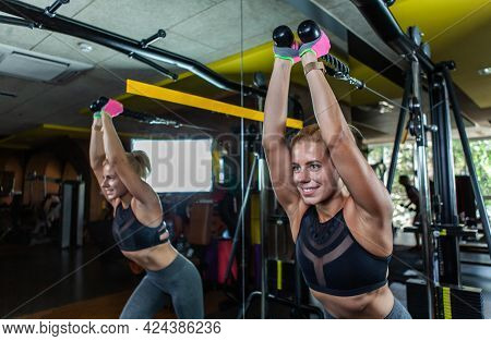 Blonde Fit Woman Doing Exercises For Triceps On Cable Machine At The Gym.