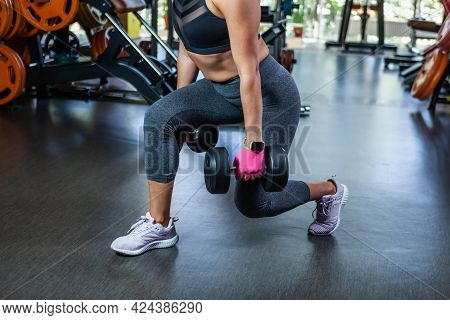 Fit Woman Exercising With Dumbbells In Her Hands. Dumbbell Lunges In The Gym. Leg Workout