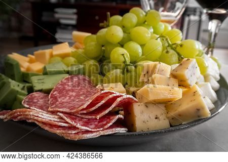 Cheese, Salami, Grapes On A Plate. Different Types Of Cheese, Cut Into Pieces. Wine Snack. Treat For