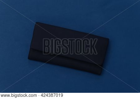 Black Leather Female Clutch Handbag On Classic Blue Background. Top View