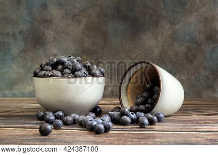 Blueberries In A Cup, On A Wooden Table. The Berries Are Scattered On The Table. Blurred Background.