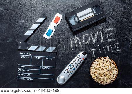 Movie Time. Movie Clapper Board,  3d Glasses, Popcorn Bowl, Video Cassette And Tv Remote On Chalk Bl