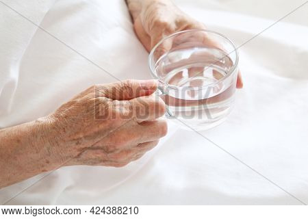 Elderly Woman With Glass Of Clean Water In Wrinkled Hands. Concept Of Thirst, Diet At Retired, Water