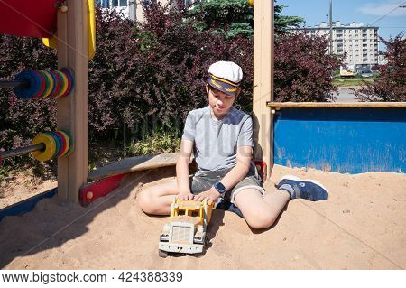 Teenager Playing In Sandbox With Yellow Toy Truck On A Sunlit Summer Playground.