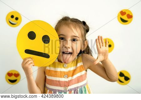 A Funny Girl Holds A Cardboard Sad Emoticon In Her Hands And Shows Her Tongue While Laughing. World
