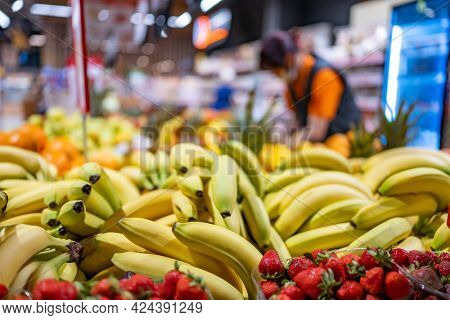 Colorful fruits and berries on farmer market and seller on blured background. Bananas and strawberry sold at grocery bazaar. Various healthy local and exotic food