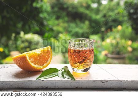 A Shot Of Traditional Belgian Tangerine Liqueur On A Windowsill Against The Backdrop Of A Summer Gar