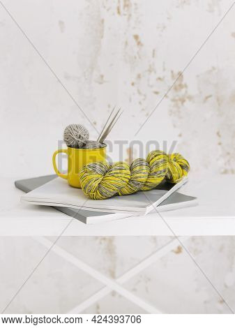 Hand Knitting With Needlesand Skein Of Yarn On A White Background. Concept For Handmade And Hygge Sl