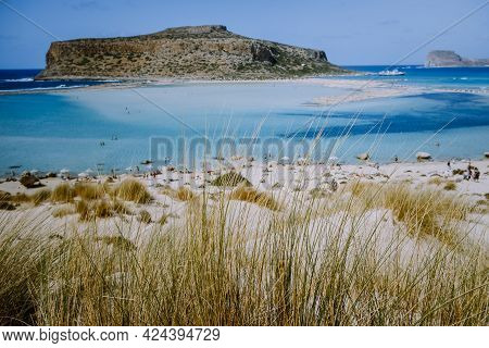 Crete Greece, Balos Lagoon On Crete Island, Greece. Tourists Relax And Bath In Crystal Clear Water O