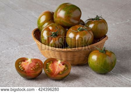 Basket with ripe red and green striped whole and half fresh tomatoes close up