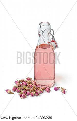 Aromatic rose bud water in a glass bottle with dried rose buds in front isolated on white background