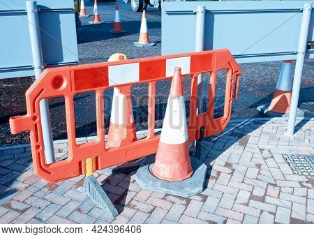 Red Reflective Traffic Cones And Safety Barrier Installed During Roadworks To Separate Safe Walking