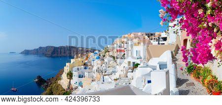 Traditional Greek Village Oia Of Santorini, Street Against Aegan Sea And Caldera, Greece With Flower