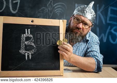 Bitcoin Coins Conspiracy Theories In The Hand Of A Conspiracy Theorist Sitting At A Chalkboard Table