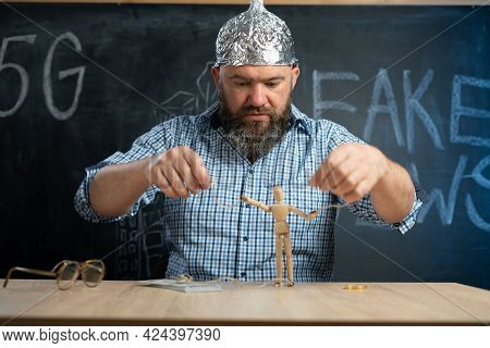 A Distraught Schizophrenic Conspiracy Theorist In A Protective Foil Cap Controls A Man - A Toy. Cons