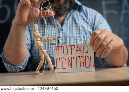 Close-up Of A Crafty Puppet In The Hands Of A Conspiracy Theorist Man Sitting At The Table. Man Cont