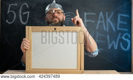 Stupid Conspiracy Theory Guy In A Foil Hat Holds A Blackboard With Space For Text. A Bearded Conspir