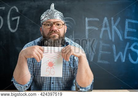 Conspiracy And A Man Sits At The Blackboard And Holds A Sign 5g In His Hands. Chalk Board In The Bac