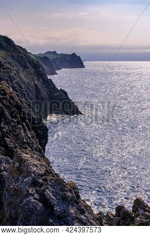 Rock Cliffs Jutting Into The Blue Sea In The Cantabrian Sea. Santander Spain.