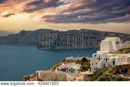 Santorini Island, Greece. Oia Caldera Over Aegean Sea, Orange Color Cloudy Sky, Calm Sea