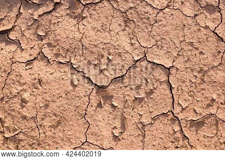 Close-up Of The Soil. Dry Natural Clay Of Red Color In Cracks.