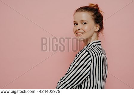 Relaxed Brunette Teenage Girl Dressed In White And Black Shirt With Hair In Bun, Looking At Camera W