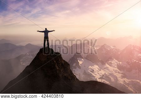 Adventure Composite. Adventurous Man With Open Hands Is Hiking On Top Of A Mountain. Colorful Sunset