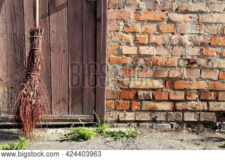 Garden Tool. Old Broom On Brick Wall And Wooden Doors Background. Close-up Object