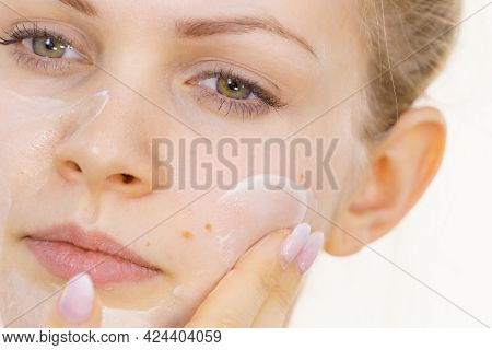 Young Woman Applying Cream Cosmetic, Mask Moisturizing To Her Face. Beauty Treatment. Skincare.