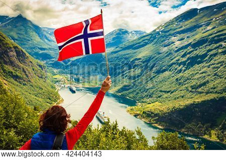 Female Tourist With Norwegian Flag Enjoying Scenic View Over Fjord Geirangerfjord With Cruise Ship.