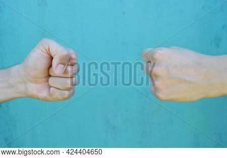 Male And Female Hands Show Each Other Fists In Close-up On A Blue Background. Hands Play A Game Of