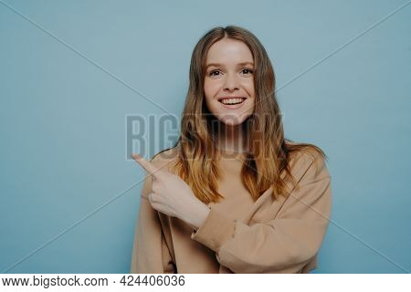 Smiling Pretty Young Female With Balayage Hair In Loose Casual Sweater Pointing Her Finger Up At Som