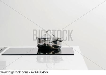 Shiny Metal Pot On Glass Induction Cooktop Built In Kitchen Counter, Food Being Cooked And Prepared,
