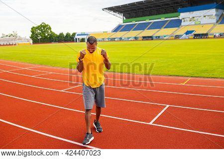 Joyful Young African American Male In Sportswear Triumphant Smiling Celebrating Goal, Match Win Scre