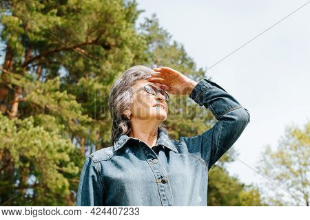 Portrait Of A Joyful Mature Woman With Glasses Outdoors. Senior Woman Standing In Nature And Squinti