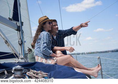 Happy smiling couple sitting on sailing boat enjoying summer and vacation travel.