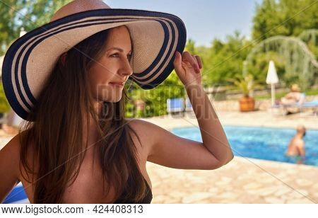 Happy woman in straw hat and swim wear at poolside in summer, smiling. Copyspace.