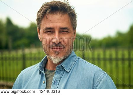 Portrait of mature age, middle age, mid adult man in 50s, happy confident smile, outdoor at home in garden.