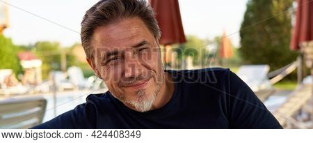 Portrait of mature age, middle age, mid adult man in 50s, happy confident smile, outdoor.